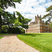 Downton Abbey's Highclere Castle with Gravel Walking Path. Highclere Castle, in Hampshire, is the home of the Earl and Countess of Carnarvon and is used in the filming of the British TV series Downton Abbey. This shot features ones of the walking paths used in the opening credits.