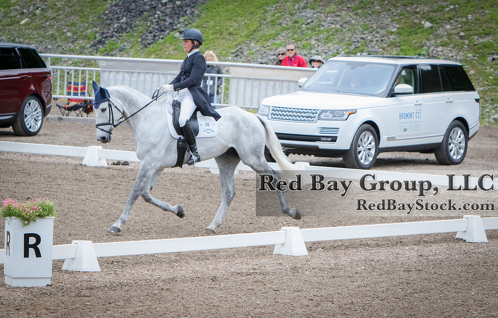 Kylie Lyman (USA) and Sacramento with a 2016 Range Rover on display in the background during Friday dressage at the Jaguar Land Rover Bromont CCI in Bromont, Quebec.