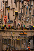 A collection of domestic tools stored on the wall of a small farmstead garage. Nailed into a home-made board attached to the wall of this shed, the tools have their own specialplace, marked by drawn shapes of each item allowing easy replacement after use. Hammers, chisels, screw drivers, hacksaws, alan keys and spanners all their own location giving the idea of a well-organised workshop.