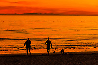 Women walking with a dog at sunset at Hendry's Beach (Arroyo Burro County Beach Park), Santa Barbara, California USA.
