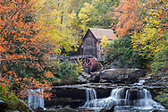 The old grist mill at Babcock State Park in West Virginia, lies nestled within a curtain of vivid autumn foliage above the scenic Glade Creek.