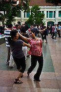 A large group of Vietnamese meet in the morning at a park in Hanoi to practice tango dancing, Vietnam, Southeast Asia