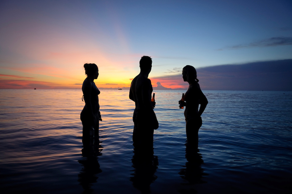 Three young adults at sunset on Koh Tao, Thailand