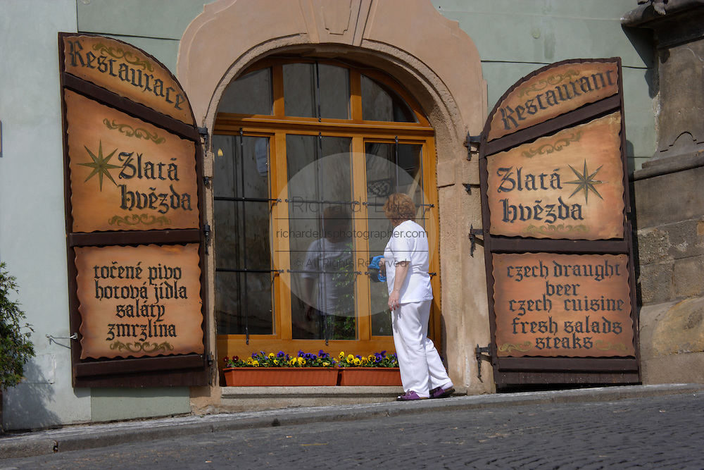 A cafe along Nerudova Street advertises their menu on decorative signs in Prague, Czech Republic.