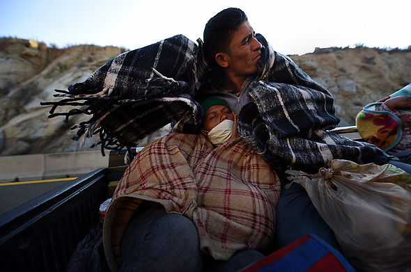 November 20, 2018 - Mexicali, Mexico - JONATAN MATAMOROS, 36 and his wife SARA ARTIAGA, 31 with their infant son JOE MIGUEL ARTIAGA, 18 months old from Honduras, hitch a ride with others from migrant caravan that had stopped to rest in Mexicali, Mexico. They endure the cold wind as they drove through La Rumorosa mountain road to a shelter in Tijuana where they will wait in hopes of crossing the border to America.  They started October 12 on their journey with caravan. (Credit Image: © Carol Guzy/ZUMA Wire)