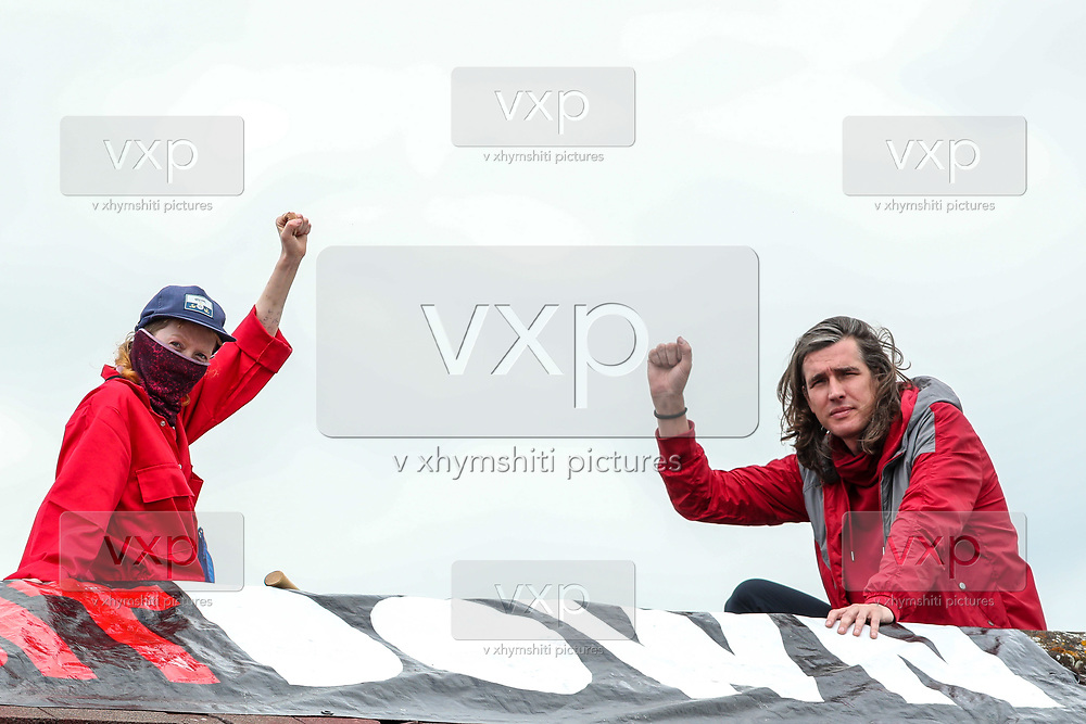 """Tamworth, United Kingdom, July 12, 2021: Activists from the """"Palestine Action"""" activist group gesture after they scaled the roof, daubed blood-red paint and smashed the windows across the Elite KL site on Amington Industrial Estate in Tamworth early on Monday, July 12, 2021. (VX Photo/ Vudi Xhymshiti)"""