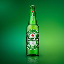 Bottle of cold Heineken lager beer on a green reflective background.