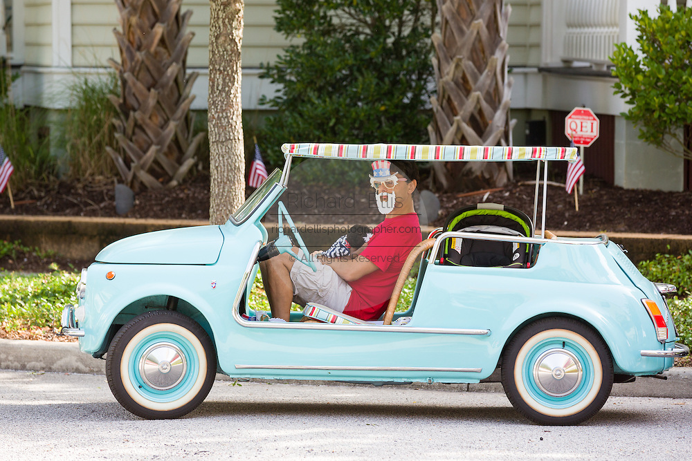 A resident wearing an Uncle Sam mask waits in a Fiat 500 Jolly for the start of theI'On neighborhood Independence Day parade July 4, 2015 in Mt Pleasant, South Carolina.