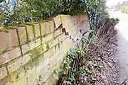 Impact damage to red brick garden wall caused by vehicle reversing, Suffolk, England, UK