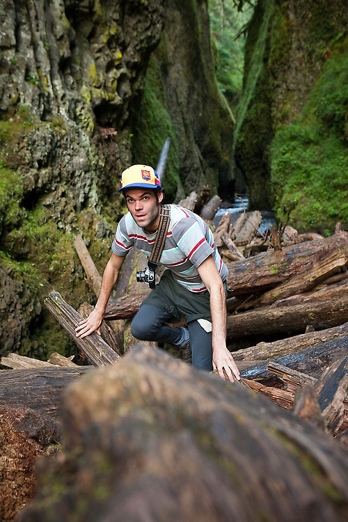 Hamilton Boyce scrambles over the log jam at the entrance to Oneonta Gorge, a mossy slot canyon cut into the bedrock in Oregon's Columbia River Gorge National Scenic Area.
