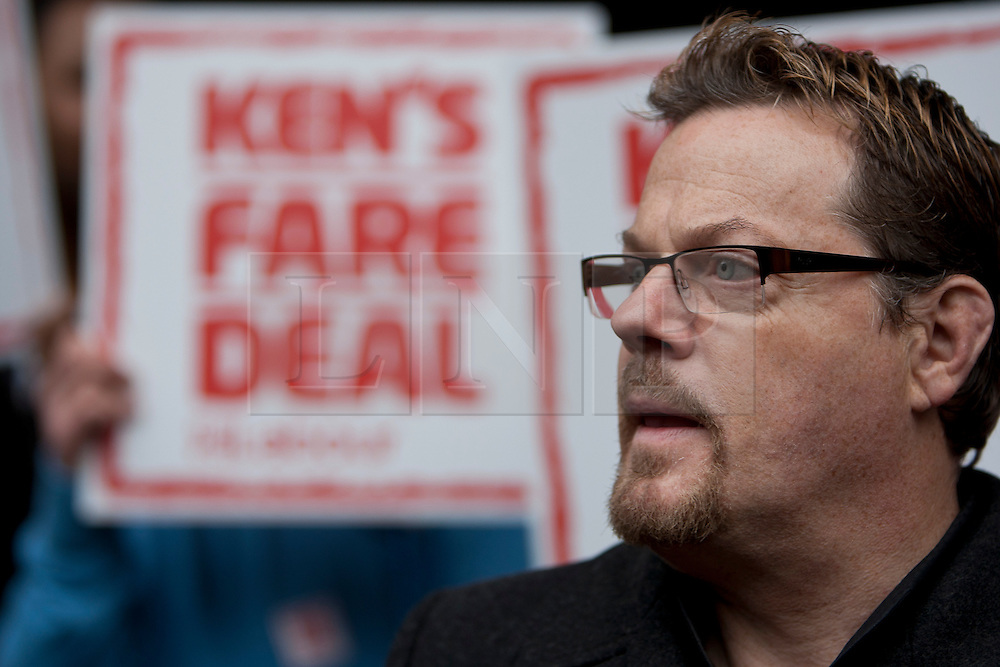 """© licensed to London News Pictures. London, UK 14/03/2012. Eddie Izzard is pictured with """"Ken's Fare Deal"""" sign as Ed Miliband and Ken Livingstone launching Labour's London election pledges for this year's mayoral election, outside London Bridge Station, today (14/03/12). Photo credit: Tolga Akmen/LNP"""