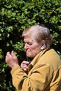 Perm, Russia, 01/06/2006..An old woman selling sunflower seeds on Lenin Street takes a break to trim her whiskers and adjust her makeup.