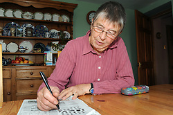 A retired woman does the crossword in her kitchen, MODEL RELEASED