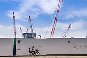 A Japanese woman rides a bicycle past the construction site for the new Olympic Stadium for the 2020 Tokyo Olympics in Gaiemmae Tokyo, Japan. Friday May 12th 2017