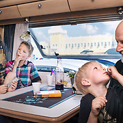 """Antero Rossi parked his caravan right in the parking lot of the shopping paradise. Grandchildren Johannes, Jeremias and Eelis got lollypops for dessert. """"I'm not sure what brings us here every year. The mall is too big to find anything"""", grandmother Eeva Rossi says."""