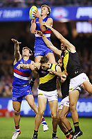 Aaron Naughton of the Bulldogs takes a screamer over Noah Balta of the Tigers during the round seven AFL match between the Western Bulldogs and the Richmond Tigers at Marvel Stadium on May 04, 2019 in Melbourne, Australia.