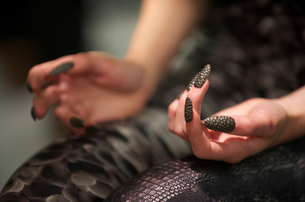 A model awaits custom made lizard skin themed finger nails to dry backstage before the Aminaka Wilmont spring 2011 fashion show at the On/Off venue in Bloomsbury Square, London on 17 September 2010.