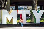 A woman poses by the city sign in the Macroplaza Grand Plaza in the Barrio Antiguo neighborhood of Monterrey, Nuevo Leon, Mexico.