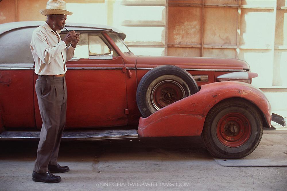 A Cuban man stops to light his cigar in Havana, Cuba.
