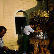 May 09, 2013 - Yangon, Myanmar: A devotee offering water to a buddha statue as part of a ritual in one of the many shrines at Sule Pagoda in Yangon. CREDIT: Paulo Nunes dos Santos
