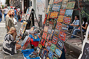 Female tourist looking at items for sale, San Telmo market, Buenos Aires, Federal District, Argentina.