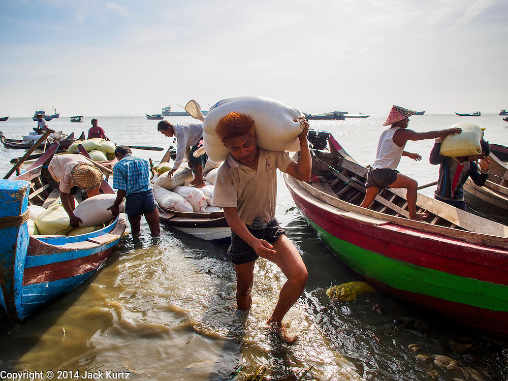10 NOVEMBER 2014 - SITTWE, MYANMAR: Porters unload small rice boats bringing rice into the rice market in Sittwe, Myanmar. Sittwe is a small town in the Myanmar state of Rakhine, on the Bay of Bengal.    PHOTO BY JACK KURTZ