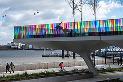 © Licensed to London News Pictures. 27/03/2021. London, UK. People exercise on the new installation titled Hundreds and Thousands by artist Liz West for The Tide. The outdoor art work is installed on the new elevated riverside trail, The Tide, on the Greenwich Peninsula. 700m of the walkways glass balustrades are covered by a ribbon of colour. Hundreds and Thousands is presented by NOW Gallery.<br />  credit: Ray Tang/LNP