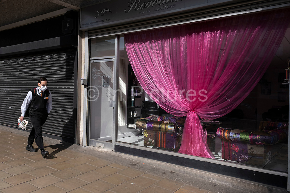 Man wearing a face mask passes a pink curtain in the window of a closed hair dressers as the third national coronavirus lockdown continues, during the first days of the easing of lockdown restrictions on 30th March 2021 in Birmingham, United Kingdom. After months of lockdown, the first signs that life will start to get back to normal begin, with more people enjoying the company of others in public, as the rule of six starts the first stage of lockdown ending.