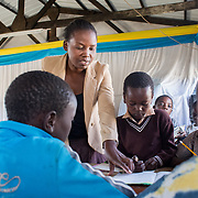 INDIVIDUAL(S) PHOTOGRAPHED: Judith Banda (left) and unknown (right). LOCATION: Chibolya Community School, Chibolya, Lusaka, Zambia. CAPTION: Community leader Judith Banda at Chibolya Community School in Lusaka. A block of classrooms was constructed at the school as part of Build It International's Training into Work & Community Building programme. Build It International is a charity that trains unemployed young people in Zambia to become builders, while at the same time building vital schools and clinics in communities with little or nothing by way of resources.