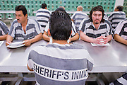 """06 NOVEMBER 2006 - PHOENIX, AZ:  Maricopa County prisoners sit in the dayroom at the jail and wait to return to their tents after English class. Maricopa County Sheriff Joe Arpaio is offering intensive two week English classes in the Maricopa County Jails so county prisoners can communicate with Detention Officers. The classes teach """"jail English"""" so inmates can report medical problems, request their lawyers, request bedding etc. There are more than 1,000 illegal immigrants in the county jail system. In 2011, the US Department of Justice issued a report highly critical of the Maricopa County Sheriff's Department and the jails. The DOJ said the Sheriff's Dept. engages in widespread discrimination against Latinos during traffic stops and immigration enforcement, violates the rights of Spanish speaking prisoners in the jails and retaliates against the Sheriff's political opponents.      PHOTO BY JACK KURTZ"""