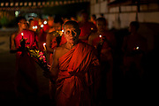 Buddhist monks carrying floral offerings leading a candlelit procession from the temple at dusk, Wat Si Saket, Vientiane, Laos