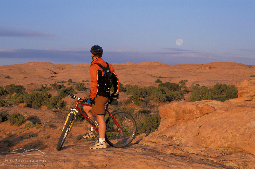 Moab, UT..Mountain biking on the Moab Slickrock Bike Trail.  Navajo Sandstone.  BLM land.  Full moon.