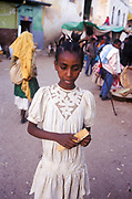 Girl with braids in her hair. The ancient walled city of Harar. Situated in Eastern Ethiopia it is considered to be the fourth  holiest city in Islam with 82 mosques. It is a major commercial centre linked by trade routes with the rest of Ethiopia and the entire Horn of Africa.  Ethiopia