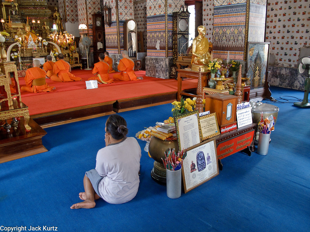 """Mar. 9, 2009 -- BANGKOK, THAILAND:  A woman prays in Wat Arun in Bangkok. Wat Arun is a Buddhist temple (wat) in the Bangkok Yai district of Bangkok, Thailand, on the west bank of the Chao Phraya River. The full name of the temple is Wat Arunratchawararam Ratchaworamahavihara. The outstanding feature of Wat Arun is its central prang (Khmer-style tower). It may be named """"Temple of the Dawn"""" because the first light of morning reflects off the surface of the temple with a pearly iridescence. Steep steps lead to the two terraces. The height is reported by different sources as between 66,80 m and 86 m. The corners are surrounded by 4 smaller satellite prangs. The prangs are decorated by seashells and bits of porcelain which had previously been used as ballast by boats coming to Bangkok from China. The central prang is topped with a seven-pronged trident, referred to by many sources as the """"trident of Shiva"""". Around the base of the prangs are various figures of ancient Chinese soldiers and animals. Over the second terrace are four statues of the Hindu god Indra riding on Erawan. The temple was built in the days of Thailand's ancient capital of Ayutthaya and originally known as Wat Makok (The Olive Temple). In the ensuing era when Thonburi was capital, King Taksin changed the name to Wat Chaeng. The later King Rama II. changed the name to Wat Arunratchatharam. He restored the temple and enlarged the central prang. The work was finished by King Rama III. King Rama IV gave the temple the present name Wat Arunratchawararam. As a sign of changing times, Wat Arun officially ordained its first westerner, an American, in 2005. The central prang symbolizes Mount Meru of the Indian cosmology. The satellite prangs are devoted to the wind god Phra Phai..Photo by Jack Kurtz / ZUMA Press"""