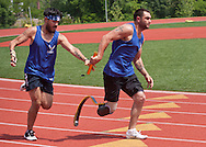 West Point, New York - Air Force's Daniel Crane, left, hands the baton to teammate Nicholas Dadgostar in the 400-meter relay at the 2014 Army Warrior Trials at the United States Military Academy Preparatory School on Tuesday, June 17, 2014.<br /> Hosted by the U.S. Army Warrior Transition Command (WTC), the trials determine which athletes will compete at the 2014 Warrior Games this fall in Colorado Springs, Colorado.