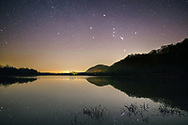 The great hunter Orion rises above a pond in the starry sky above the marsh at Green Bottom, West Virginia
