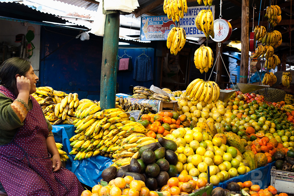 A women smiles at her fruit stand in a big food market in Cusco, Peru.