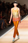 Shiny orange pants with a glittery top in soft pastels.