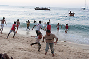 Local children at sunset play in the water in the islands main settlement Stone Town on 6th December 2008 in Zanzibar, Tanzania. Each day these kids gather to jump in the waves, cool off and throw each other into the ocean. Zanzibar is a small island just off the coast of the Tanzanian mainland in the Indian Ocean. In part due to its name, Zanzibar is a travel destination of mystical reputation, known for its incredible sealife on its many reefs, the powder white coral sand beaches and the traditional cultivation of spices.