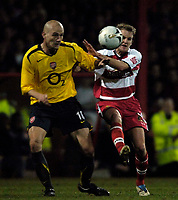 Photo: Jed Wee.<br /> Doncaster Rovers v Arsenal. Carling Cup. 21/12/2005.<br /> <br /> Doncaster's James Coppinger (R) challenges Arsenal's Pascal Cygan for possession.