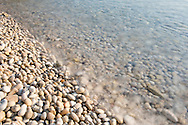 Sea water washing over smoothe rounded stones on Orkos Beach on the island of Paxos, The Ionian Islands, The Greek Islands, Greece, Europe