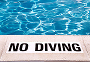 Edge of a swimming pool with warning sign that reads No Diving.