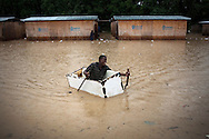 A boy uses a broken refrigerator to paddle around a flooded area in Leogane, Haiti, as Hurricane Tomas passes through.