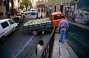 A local delivery van full of gas cylinders struggles to round an uphill corner in central Lisbon, Portugal. The narrow streets, not designed for heavy traffic, still do not accommodate smaller vehicles. A tram waits for the obstructing truck to clear the tracks and rails and onlookers stop to see how the driver manages to get round without spilling its dangerous cargo.