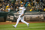 Oakland Athletics third baseman Trevor Plouffe (3) watches Miami Marlins baserunners after making a catch at Oakland Coliseum in Oakland, Calif., on May 23, 2017. (Stan Olszewski/Special to S.F. Examiner)