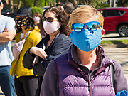 09 MAY 2020 - DES MOINES, IOWA: People wearing face masks line up and social distance at a drive through farmers' market in Des Moines. People who walked up voluntarily social distanced. The Governor allowed farmers' markets across the state to reopen last weekend, but limited them to selling just food stuffs. They are not allowed to have entertainment or sell non-food items. Most farmers' markets in Iowa are taking a wait and see approach to reopening. The Downtown Farmers Market in Des Moines announced they won't reopen until July. Three vendors set up their own drive through farmers' market in the parking lot of Des Moines theatre Saturday. Hundreds of people got in line to buy fresh produce and artisan cheese. More than 11,670 people have tested positive for COVID-19 in Iowa and more than 250 have died from the disease.    PHOTO BY JACK KURTZ
