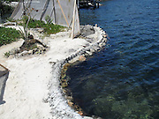 """Eco-pioneer Richard """"Rishi"""" Sowa designed and built an artificial island kept afloat by 100,000 plastic bottles.<br /> <br /> Spiral Island II is actually Rishi Sowa's second artificial island. He built the first one in 1998, near Puerto Aventuras, using 250,000 plastic bottles to keep it afloat. Sadly, his recycled island was destroyed in 2005, when Hurricane Emily passed through the area. Most of Spiral Island was washed up on the beach, but Sowa decided to build a whole new island, in a safer area.<br /> <br /> And that's how Spiral Island II came to be. With the help of volunteers, Rishi Sowa gathered around 100,000 plastic bottles and hand-built his second recycled island, in a lagoon that offers protection from bad weather. The new island features a house, beaches, 2 ponds and a solar-powered waterfall, but its creator says Spiral Island II is and always will be an eco-work-in-progress. Although smaller than its predecessor (only 20 meters in diameter), you can expect the new Spiral Island to increase in size, significantly.<br /> <br /> One of the most impressive DIY projects ever attempted, Spiral Island has inspired volunteers to come to Mexico and help Rishi Sowa improve his creation. But while some believe it a perfect environmental design, built entirely of recycled materials, there is some controversy surrounding Spiral Island. There are those who believe that if the island gets destroyed by a hurricane, again, the materials used to build it (mainly plastic bottles, sand, mangrove plants) will litter the waters of the Atlantic.<br /> Photo Shows: coral and concrete edges<br /> ©Spiral Island /Exclusivepix"""