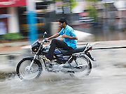 Motorbike rides through flooded street during the monsoon season, Cochin, Kerala, India