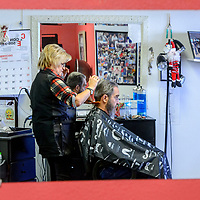 A mirror reflects Grants mayor Modie Hicks receiving a haircut from Clorinda Brito at Clo's Hair Design in Grants Thursday. Hicks had his hair cut after a fundraiser to benefit the Marine ROTC drill team trip to a national competition.