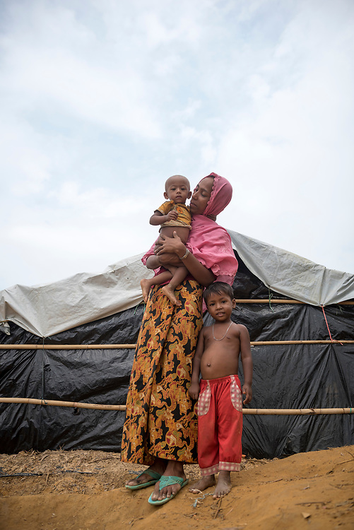 A 25-year-old Rohingya Muslim woman stands with two children outside a shelter in the sprawling Kutupalong refugee camp in Bangladesh. They are among the 600,000 who fled Myanmar in the two months beginning August 25. (October 29, 2017)